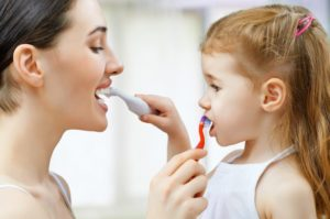 Mom teaches daughter how to brush teeth during quarantine