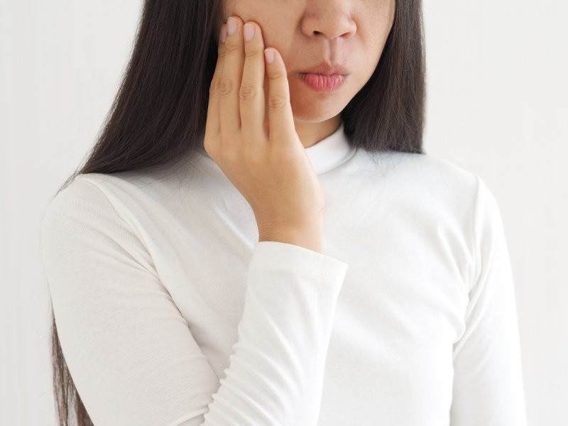 Close-up of woman in white shirt rubbing her jaw